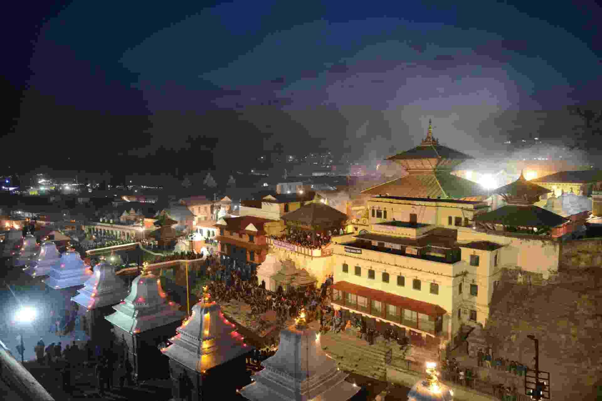 27.fev.2014 - Devotos hindus se reúnem durante o crepúsculo no templo Pashupatinath, durante o festival Maha Shivaratri, em Katmandu, no Nepal, nesta quinta-feira (27). Durante o festival, hinduístas oferecem orações especiais e jejuam. Centenas de sadhus (espécie de monges andarilhos) chegaram à Pashupatinath para participar das festividades - Prakash Mathema/AFP
