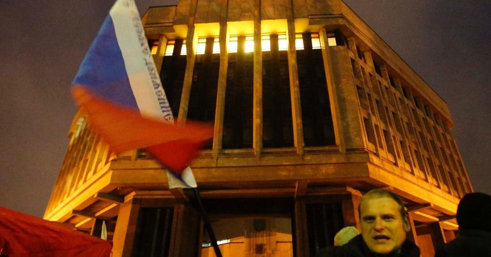 27.fev.2014 - Homem ergue bandeira russa em frente ao edifício do Parlamento durante comício pró-Rússia em Simferopol, na Crimeia, na quinta-feira (27). Homens armados tomaram o local, assim como a sede do governo e o aeroporto, colocando em estado de alerta o novo governo da Ucrânia. As tensões separatistas na região da Crimeia, de maioria russa, se intensificaram com a destituição do presidente Viktor Yanukovytch, na semana passada
