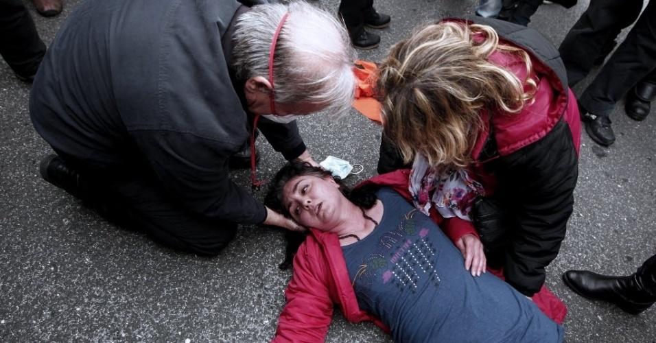 28.fev.2014 - Manifestante é atendida após sentir-se mal com o efeito do gás lacrimogêneo disparado pela polícia durante protestos na entrada do Ministério das Finanças, em Atenas, Grécia