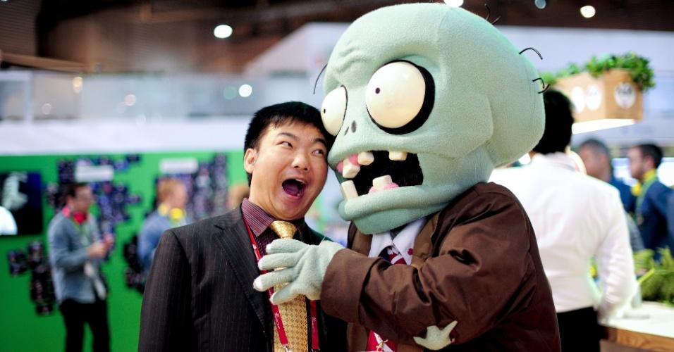 27.fev.2014 - Visitante do Mobile World Congress brinca com boneco de zumbi durante o evento. Personagem faz parte do game ''Plats vs Zombies''