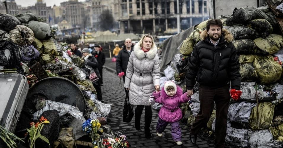 28.fev.2014 - Casal e criança caminham em meio a barricadas no centro de Kiev