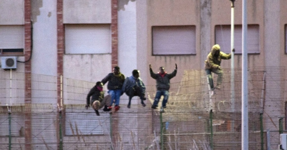 28.fev.2014 - Homens pulam cerca no enclave espanhol de Melilla, no norte da África.  Mais de 200 imigrantes africanos conseguiram nesta sexta-feira (28) entrar no enclave a partir do Marrocos, anunciou o governo de Mellila.