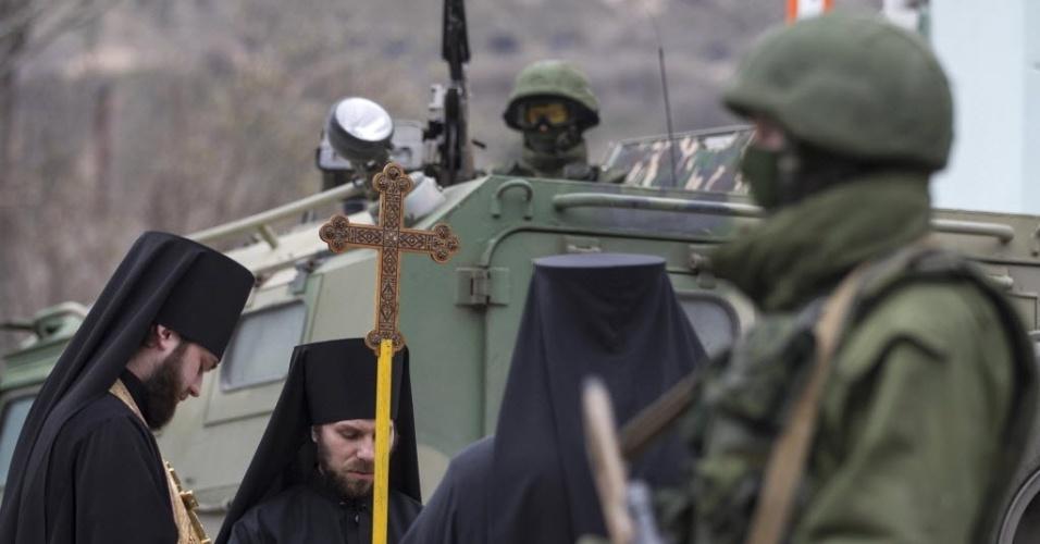 1ºmar.2014 - Monges ortodoxos rezam ao lado de soldados pró-Rússia armados que bloqueiam o acesso à base de guardar da fronteira ucraniana na Crimeia neste sábado (1º). A câmara alta do Parlamento da Rússia aprovou neste sábado (1º) o envio de tropas russas à Ucrânia