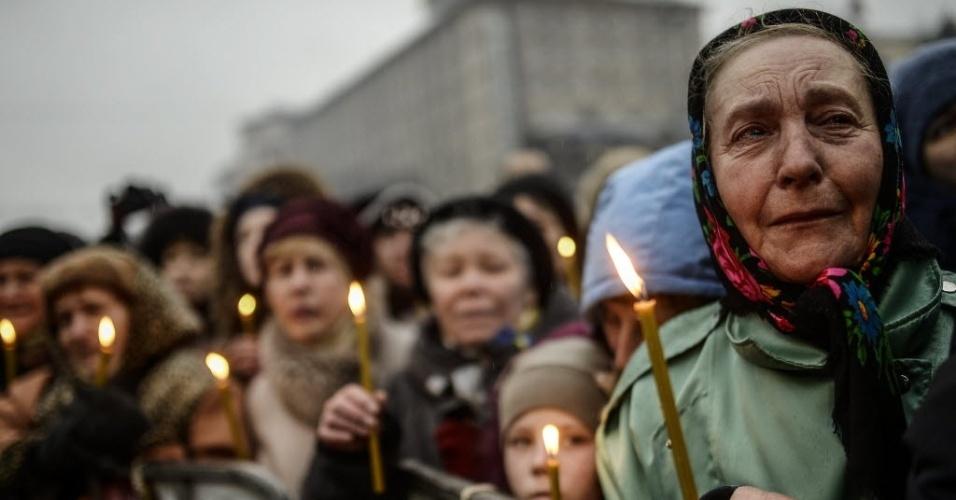 1º.mar.2014 - Pessoas seguram velas durante cerimônia fúnebre de uma vítima dos recentes confrontos com a polícia de choque na praça da Independência de Kiev. Neste sábado (1º), o Parlamento da Rússia deu ao presidente Vladimir Putin o sinal verde para enviar tropas para a Ucrânia, apesar de uma advertência de Washington de que tal implantação seria resultado em