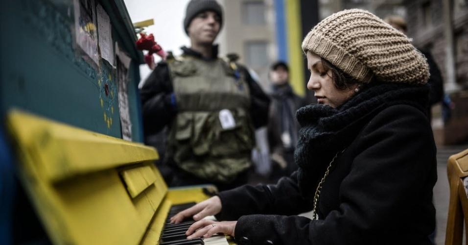 1º.mar.2014 - Uma mulher toca piano ao lado de soldados em uma rua perto da Praça da Independência de Kiev neste sábado (1º). Neste sábado (1º), o Parlamento da Rússia deu ao presidente Vladimir Putin o sinal verde para enviar tropas para a Ucrânia, apesar de uma advertência de Washington de que tal implantação seria resultado em