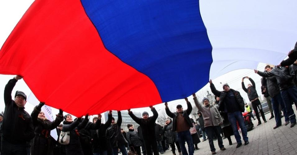 Manifestantes pró-russos balançam uma bandeira gigante da Rússia durante uma passeata na cidade ucraniana industrial de Donetsk neste sábado (1º). Mais de dez mil pessoas foram às ruas da cidade localizada no leste da Ucrânia carregando bandeiras russas. Os manifestantes declararam apoiar as aspirações da Criméia para se juntar a Rússia