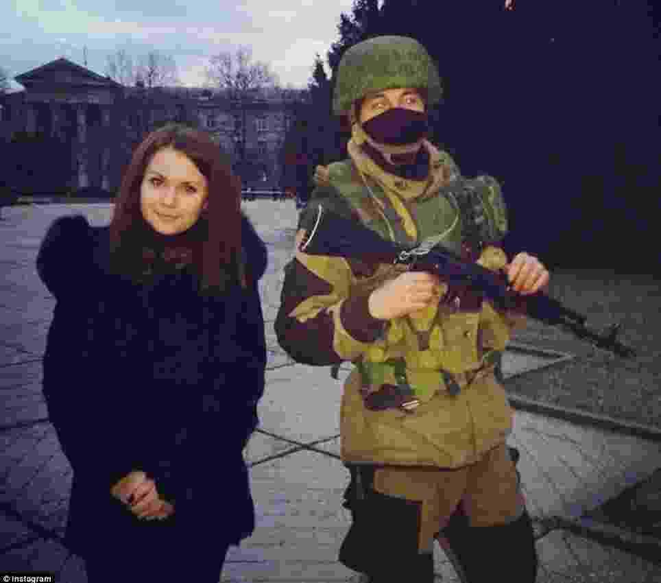 """3.mar.2014 - Jovem posta no Instagram foto sua posando ao lado de soldado russo que segura uma arma, na península da Crimeia, região autônoma no sul da Ucrânia. A área, cuja maioria da população é alinhada à Rússia, foi ocupada por tropas russas neste fim de semana, em meio a uma crise entre os dois países - Reprodução/""""Daily Mail"""""""