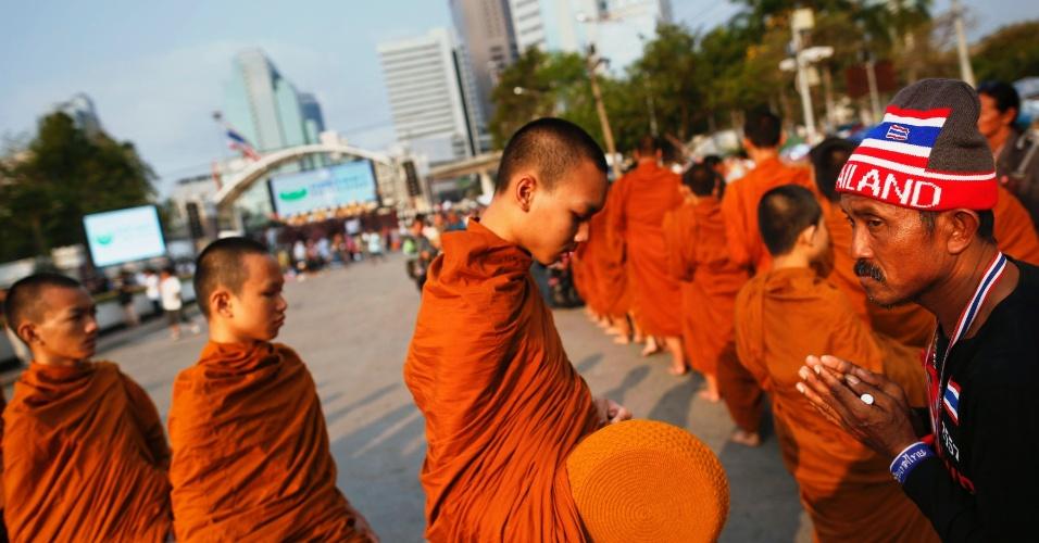 3.mar.2014 - Monges budistas coletam esmolas de manifestantes nesta segunda-feira (3) no parque Lumpini, que se transformou em acampamento após meses de protestos contra o governo em Bancoc, na Tailândia. Eles exigem a renúncia da primeira-ministra Yingluck Shinawatra e a reforma do sistema político, que consideram corrupto e a serviço dos interesses do ex-premiê Thaksin Shinawatra, irmão de Yingluck