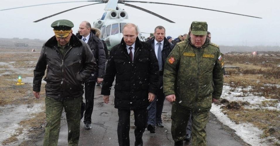 3.mar.2014 - O presidente russo, Vladimir Putin (no centro), e o ministro da Defesa russo, Sergei Shoigu (à esq.), e comandante do Distrito Militar Ocidental, Anatoly Sidorov (à dir.), na chegada ao campo de testes militares em Kirillovsky, região de Leningrado, na Rússia, nesta segunda-feira (3)