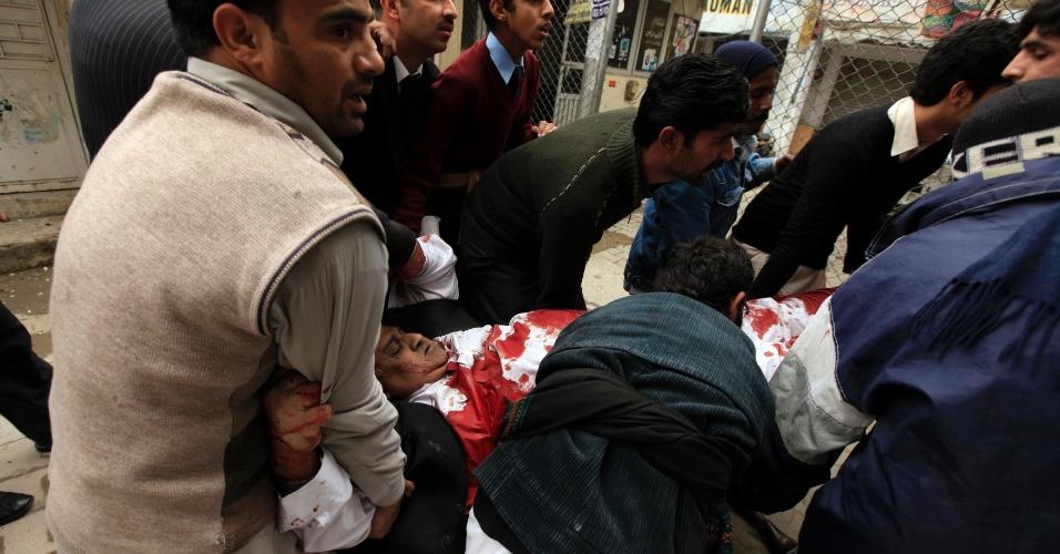 3.mar.2014 - Pessoas socorrem homem ferido em atentado à bomba ao tribunal distrital de Islamabad, no Paquistão, nesta segunda-feira (3). Pelo menos 11 pessoas, incluindo um juiz, foram mortos no ataque no centro da capital paquistanesa