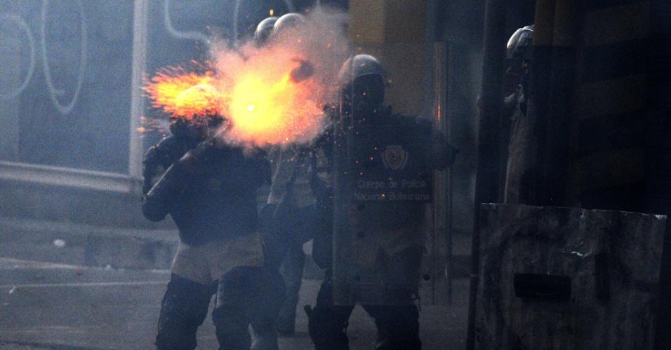 3.mar.2014 - Policiais da Guarda Nacional venezuelana atiram contra manifestantes de oposição durante confronto após protesto antigoverno