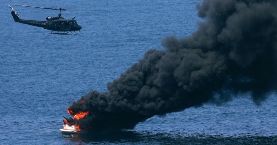 3.mar.2014 - Um helicóptero da polícia voa sobre um barco em chamas perto da praia da Barra da Tijuca, no Rio de Janeiro, nesta segunda-feira (3). Nenhuma vítima foi registrada no acidente do barco de propriedade privada e a causa do incêndio ainda está sob investigação, de acordo com a mídia local