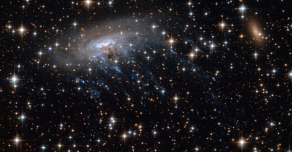 """4.mar.2014 - CRIME CÓSMICO - Esta nova imagem do telescópio Hubble mostra a galáxia espiral ESO 137-001 ao se mover para o coração do aglomerado de galáxias Abell 3627. Durante o movimento, as espirais são """"rasgadas"""", deixando faixas azuis brilhantes de estrelas jovens quentes, que estão sendo arrancadas da galáxia por seus arredores. ESO 137-001 faz parte da Norma Cluster, um aglomerado de galáxias perto do centro do Grande Atrator, uma região do espaço que ganhou seu nome por ser tão grande e ter uma força gravitacional tão forte que ele está puxando galáxia inteira para ele. Esta região está localizada a cerca de 200 milhões de anos-luz da nossa galáxia, a Via Láctea"""