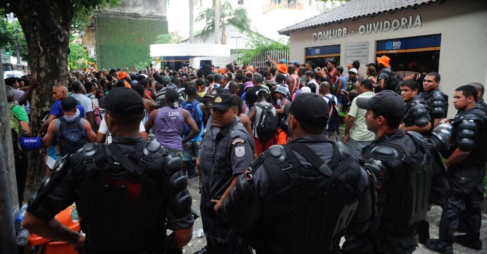 5.mar.2014 - Policiais observam protesto de garis em frente à sede da Comlurb (Companhia Municipal de Limpeza Urbana), na zona norte do Rio, nesta quarta-feira (5)