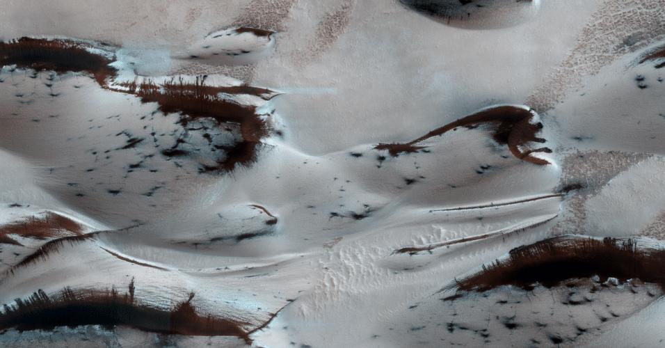 6.mar.2014- DUNAS MARCIANAS NA PRIMAVERA - As dunas no norte de Marte estão começando a aparecer sob a cobertura sazonal de inverno de dióxido de carbono congelado (seco). Escuras, as encostas voltadas ao Sul absorvem o calor do Sol. Nas partes mais íngremes, onde não há gelo, a areia escorrega. As manchas escuras são locais onde o gelo rachou no início da primavera e liberou areia. Logo, as dunas estão completamente expostas mostrando os sinais da primavera no planeta vermelho. A imagem foi obtida com a sonda MRO (Mars Reconnaissance Orbiter) da Nasa (Agência Espacial Norte-Americana)