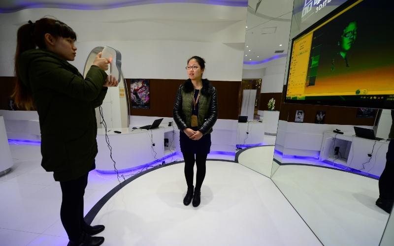 Funcionária de estúdio de impressão 3D em Nanjing (China) mostra processo de escaneamento, que leva de três a cinco minutos. Clientes podem encomendar miniatura com suas feições, que leva duas semanas para ficar pronta. A agência de notícias local Xinhua, que divulgou a foto acima, não informa o preço do produto
