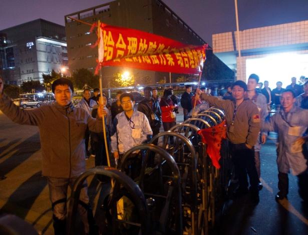 Trabalhadores da IBM seguram cartazes em fábrica da empresa em Shenzhen
