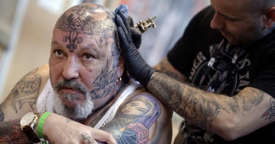 7.mar.2014 - Homem faz tatuagem na cabeça durante a segunda edição do