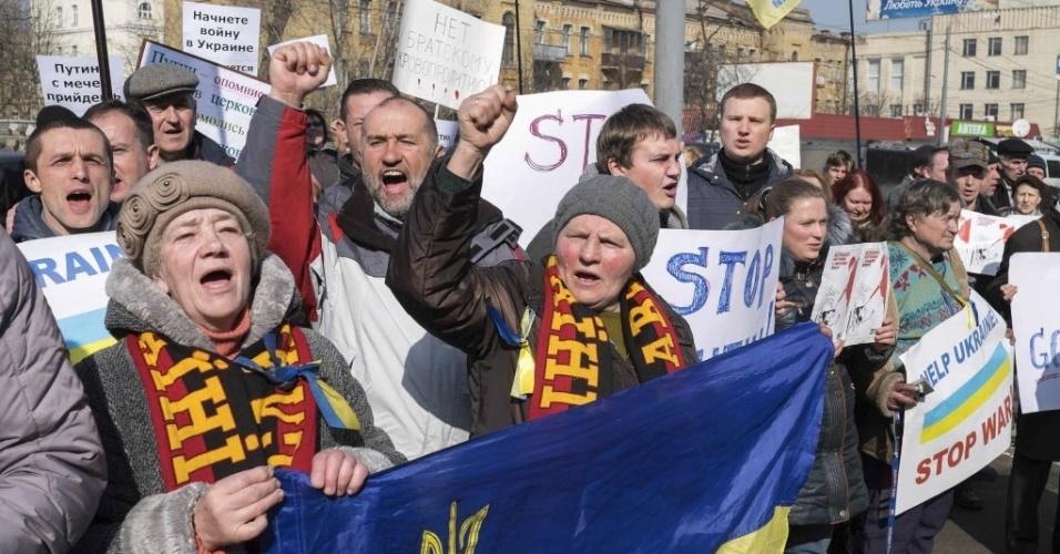 7.mar.2014 - Manifestantes seguraram cartazes durante um comício anti-guerra em frente à embaixada russa em Kiev, na Ucrânia, nesta sexta-feira (7). A Ucrânia está pronta para conversações com a Rússia, mas para isso Moscou deve primeiro retirar suas tropas, cumprir os acordos internacionais e suspender o seu apoio aos