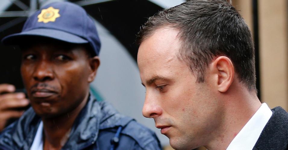 7.mar.2014 - Policial observa o atleta paraolímpico sul-africano Oscar Pistorius chegar ao tribunal em Pretória para o quinto dia de seu julgamento pelo assassinato de sua namorada, Reeva Steenkamp