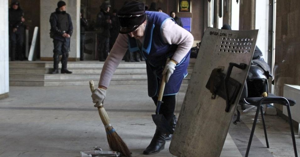 7.mar.2014 - Uma mulher limpa o chão depois de confrontos entre manifestantes pró-Rússia e policiais na sede da administração regional em Donetsk, nesta sexta-feira (7). A Ucrânia colocou a sua bandeira sobre a sede do governo na cidade oriental de Donetsk na última quinta-feira (6) e tentou tirar os manifestantes pró-Moscou que ocuparam o local