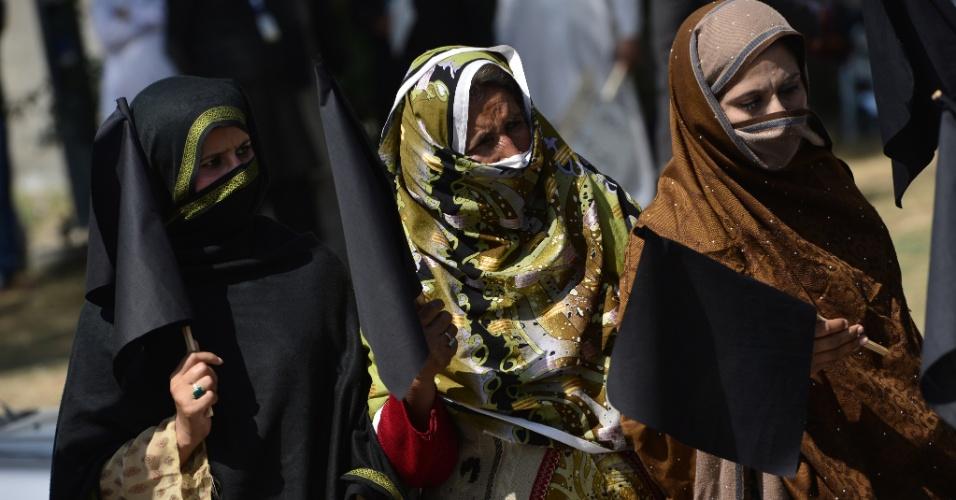 8.mar.2014 - Ativistas de direitos humanos paquistanesas seguraram bandeiras negras para destacar os direitos das mulheres no Dia Internacional da Mulher em Islamabad, no Paquistão. Centenas de mulheres e meninas são assassinadas todos os anos no país acusadas de difamar a honra de suas famílias, sem contar a violência sofrida por muitas mulheres pelos muçulmanos conservadores, que as tratam, freqüentemente, como cidadãs de segunda classe