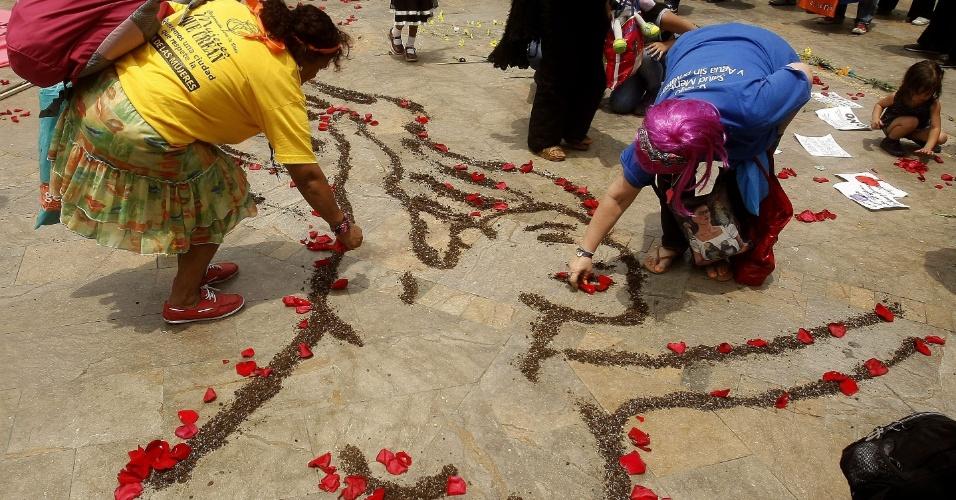 8.mar.2014 - Grupo de mulheres desenha uma figura feminina com pétalas de rosa, na praça Botero, em Medellín, na Colombia, para comemorar o Dia Internacional da Mulher