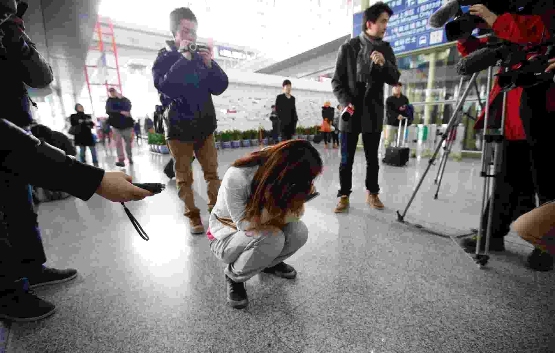 8.mar.2014 - Jornalista tenta entrevistar chinesa que chora enquanto espera por informações de passageiros do voo MH370, da Malaysia Airlines, no Aeroporto Internacional de Pequim - Kim Kyung-Hoon/Reuters