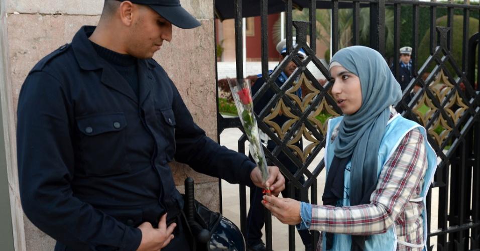 8.mar.2014 - Marroquina dá uma rosa a um policial enquanto participa de uma marcha no Dia Internacional da Mulher, em Rabat. A data remonta ao início do século 20 e tem sido celebrado pelas Nações Unidas desde 1975