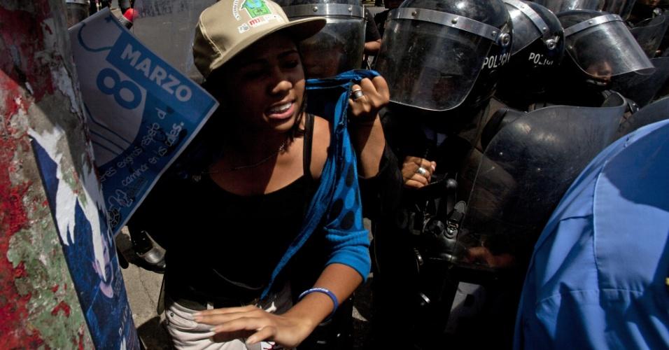 8.mar.2014 - Membros da Brigada Especial da Polícia Nacional da Nicarágua entram em choque com uma jovem que participava de uma marcha para comemorar o Dia Internacional da Mulher, em Manágua