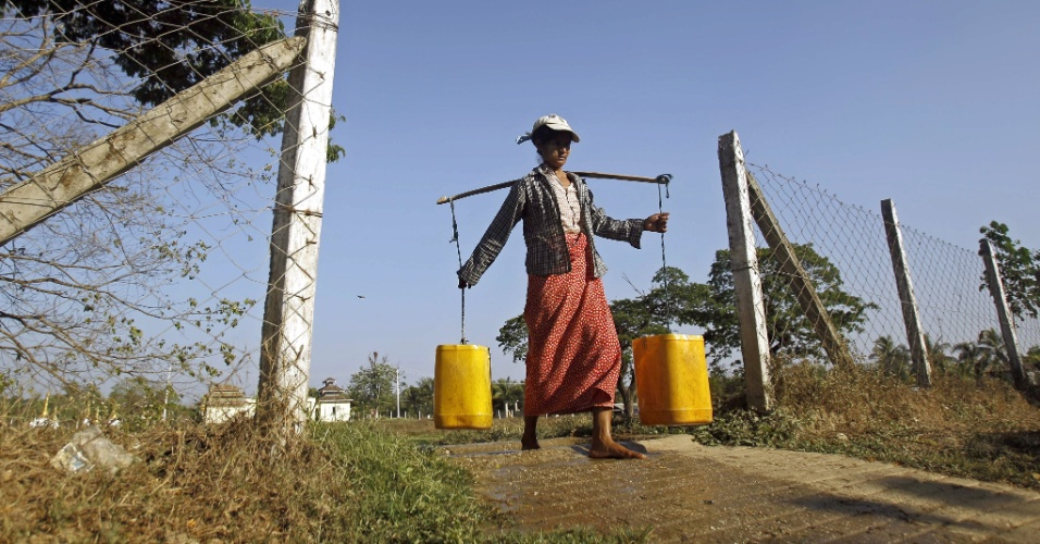 8.mar.2014 - Mianmar mulher carrega água em baldes após ter recolhido o líquido de uma lagoa nos arredores de Yangon, em Mianmar, no Dia Internacional da Mulher