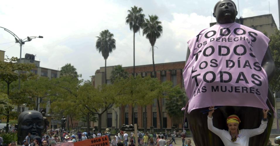 """8.mar.2014 - Mulher faz performance colocando uma camiseta com a frase """"Todos os direitos, todos os dias, todas as mulheres"""" na escultura batizada de """"Eva"""", do artista colombiano Fernando Botero, durante manifestação no Dia Internacional da Mulher, em Medellín, na Colombia"""