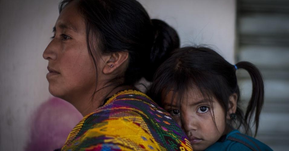 8.mar.2014 - Mulher indígena e sua filha observam marcha de centenas de mulheres como parte da celebração do Dia Internacional da Mulher, na Cidade da Guatemala, maior cidade da República da Guatemala