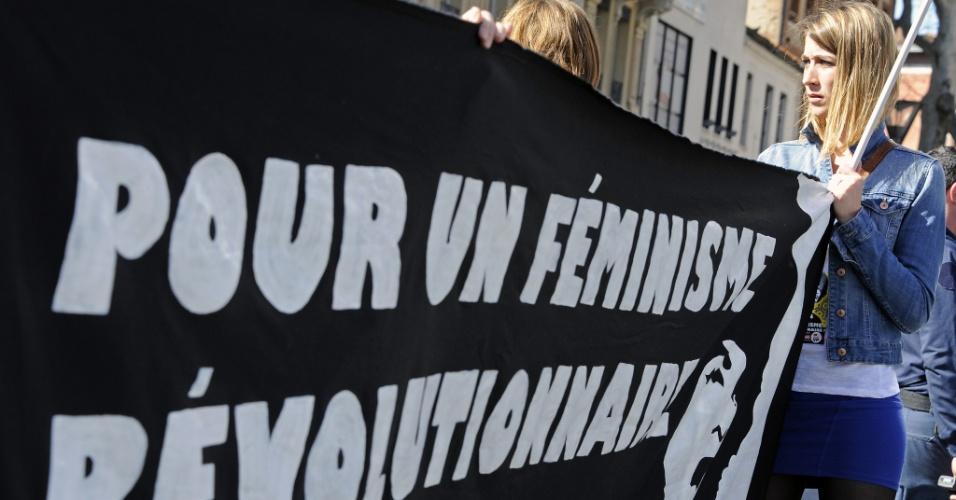 8.mar.2014 -  Mulher segura banner durante uma manifestação em Paris, na França, como parte do Dia Internacional da Mulhers. A comemoração remonta ao início do século 20 e tem sido celebrada pelas Nações Unidas desde 1975