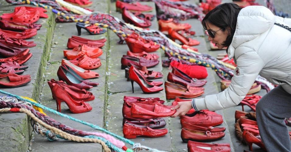"""8.mar.2014 - No Dia Internacional da Mulher, italiana coloca um sapato vermelho, símbolo da campanha """"Walk a Mile in Her Shoes"""", na praça Santa Annunziata, em Florença, Itália. O evento promove a igualdade de gênero, incentivando os homens a superarem as barreiras psicológicas e combater a violência sexual global de forma mais ampla, quebrando os estereótipos masculino e feminino"""