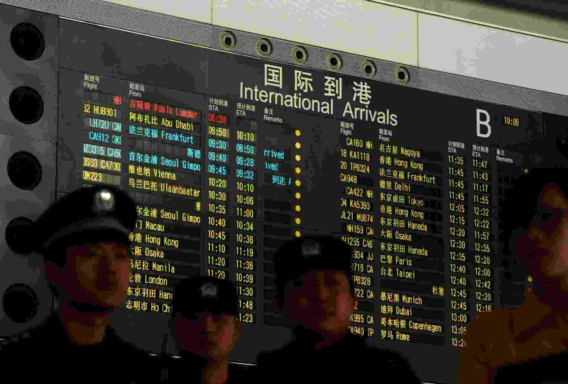 8.mar.2014 - Painel no Aeroporto Internacional de Pequim mostra, em vermelho, o voo MH370, da Malaysia Airlines, que leva 239 pessoas e perdeu contato com o controle terrestre - Mark Ralston/Reuters