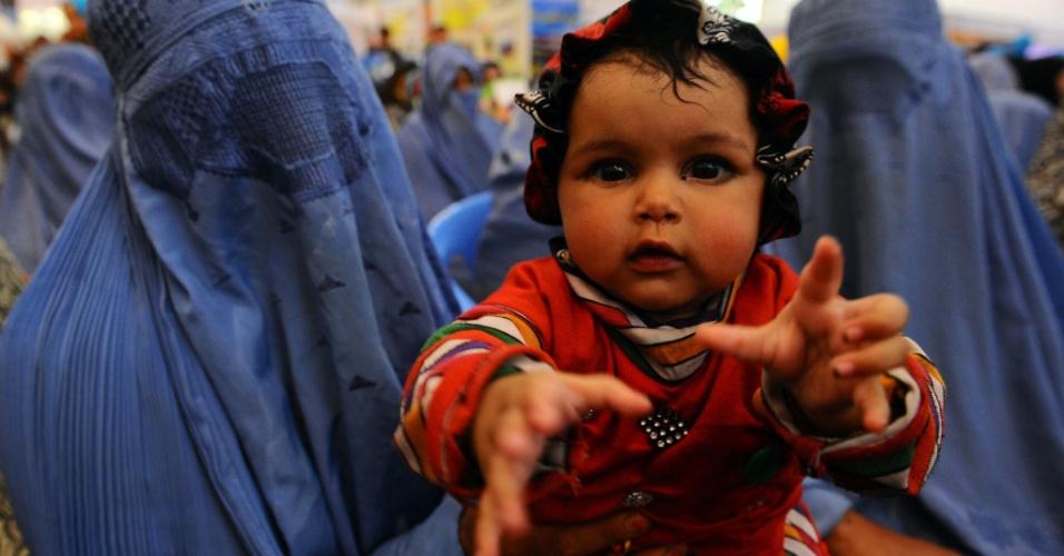 8.mar.2014 - Uma mulher afegã segura seu bebê enquanto participa de evento para marcar o Dia Internacional da Mulher na província de Herat, no Afeganistão. O Dia Internacional da Mulher, antes chamado de Dia Internacional do Trabalho da Mulher, celebra as conquistas econômicas, políticas e sociais das mulheres dopassado, presentes e futuro