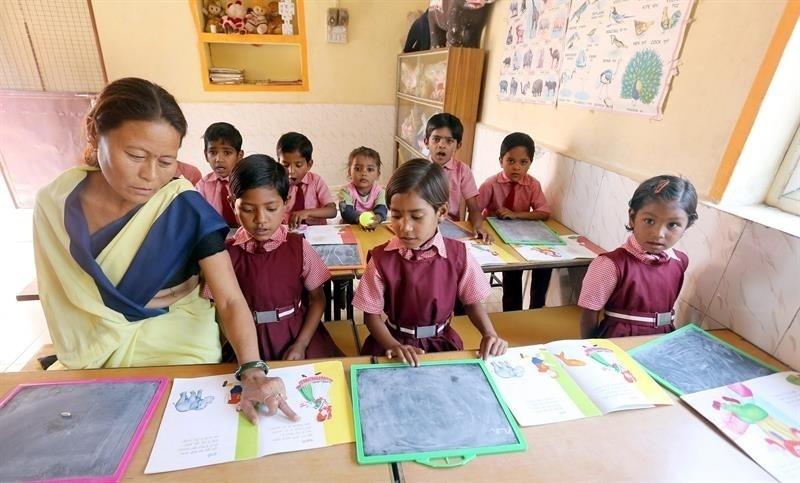 8.mar.2014 - Uma mulher que está presa ensina crianças de outras mulheres presas em uma escola no interior do campus da prisão central de Bhopal, na Índia, no Dia Internacional da Mulher. Há cerca de 147 mulheres presas no local com seus 26 filhos