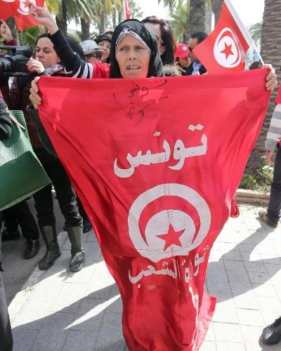 8.mar.2014 - Uma mulher tunisina detém a bandeira nacional durante uma manifestação no Dia Internacional da Mulher, em Túnis, na Tunísia. Cerca de cem mulheres marcharam nas ruas usando slogans contra o terrorismo e exigindo mais liberdade