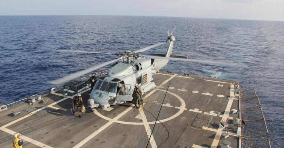 9.mar.2014 - O helicóptero Sea Hawk regressa ao porta-aviões USS Pinckney, após missão de busca pelos destroços do voo MH370 da Malaysia Airlines, neste domingo (9). A tripulação não conseguiu avistar sobreviventes