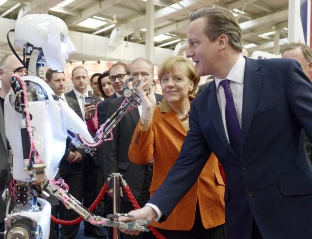 10.mar.2014 - A chanceler alemã, Angela Merkel, e o primeiro-ministro britânico, David Cameron, tocam robô apresentado na Cebit, feira de tecnologia realizada anualmente em Hanover. Durante os cinco dias de evento, que tem 3.400 expositores, são esperados cerca de 230 mil visitantes