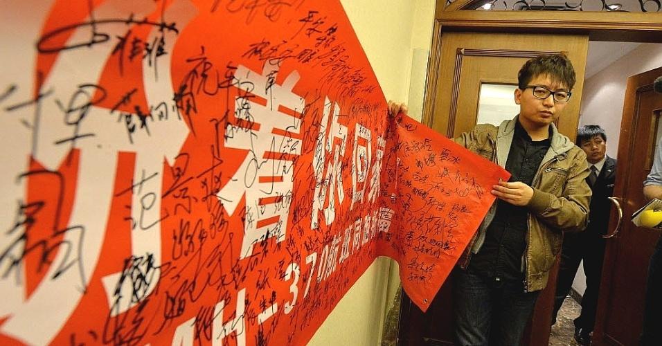 10.mar.2014 - Estudantes chineses seguram cartaz que pede mais ajuda para parentes dos passageiros do voo MH370, da Malaysia Airlines, que sumiu dos radares no último sábado (8) e segue desaparecido