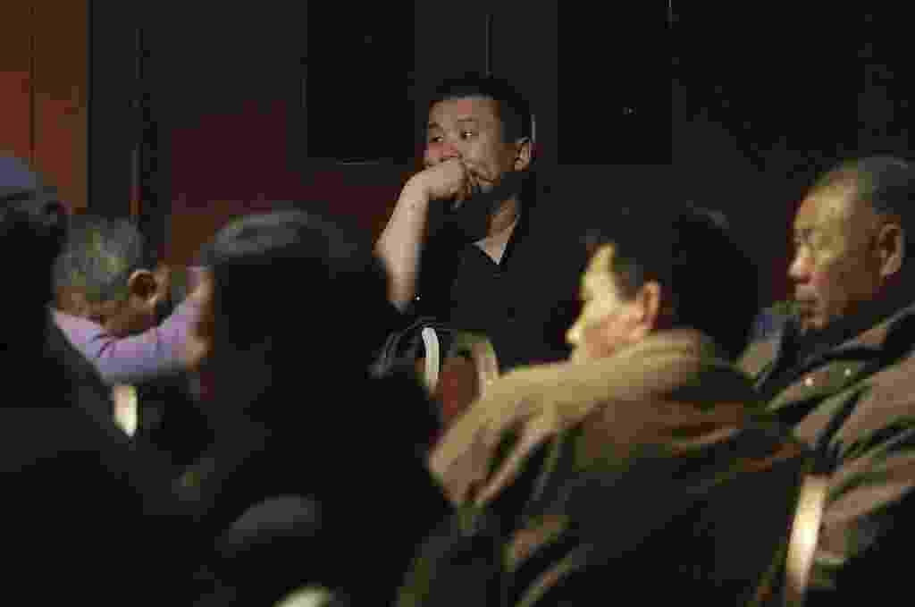 10.mar.2014 - Familiares de passageiros do voo MH370, da Malaysia Airlines, assistem ao noticiário em televisão de hotel em Pequim, na China. O governo chinês enviou agentes de segurança à Malásia para investigar o desaparecimento do avião, que levava 239 pessoas a bordo, sendo cerca de dois terços chineses - Chance Chan/Reuters