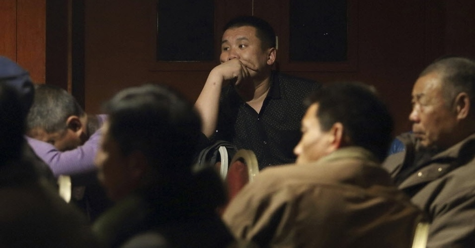 10.mar.2014 - Familiares de passageiros do voo MH370, da Malaysia Airlines, assistem ao noticiário em televisão de hotel em Pequim, na China. O governo chinês enviou agentes de segurança à Malásia para investigar o desaparecimento do avião, que levava 239 pessoas a bordo, sendo cerca de dois terços chineses
