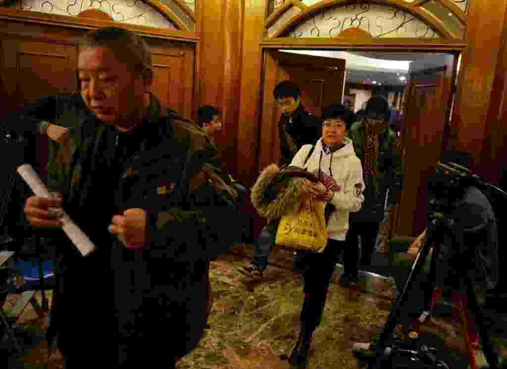 10.mar.2014 - Familiares de passageiros do voo MH370, da Malaysia Airlines, deixam sala após reunião com funcionários da companhia aérea em hotel de Pequim, na China - Mark Ralston/AFP