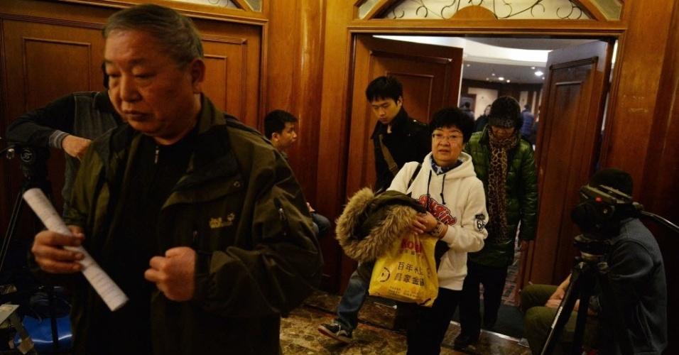 10.mar.2014 - Familiares de passageiros do voo MH370, da Malaysia Airlines, deixam sala após reunião com funcionários da companhia aérea em hotel de Pequim, na China