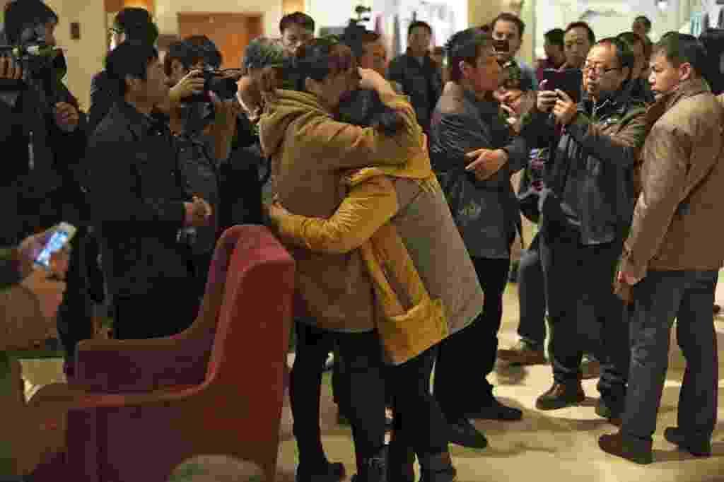 10.mar.2014 - Mulheres se abraçam enquanto aguardam notícias sobre o voo MH370, da Malaysia Airlines, que desapareceu no último sábado (8), em hotel de Pequim, na China - Mark wong/Efe