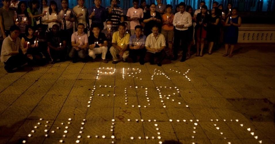 10.mar.2014 - Pessoas acendem velas em vigília pelo voo MH370, da Malaysia Airlines, em praça de Kuala Lumpur, na Malásia. Com 239 pessoas a bordo, o voo ia de Kuala Lumpur em direção a Pequim, na China, e desapareceu dos radares no último sábado (8)