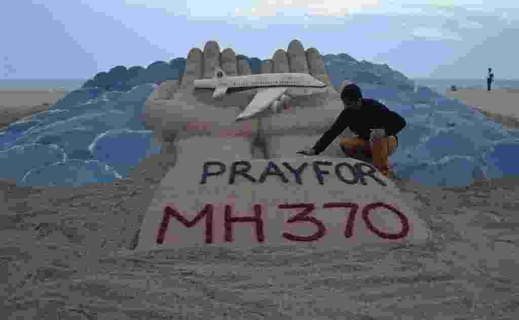 12.mar.2014 - Artista indiano de esculturas na areia, Sudarshan Pattnaik, trabalha em uma escultura pedindo que o povo reze pelos desaparecidos no avião da Malaysian Airlines, na praia dourada em Puri, no estado indiano oriental de Odisha, na Índia - Reuters