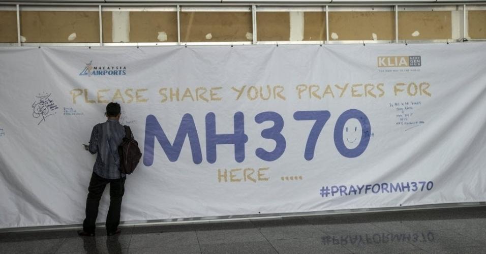 12.mar.2014 - Homem escreve mensagem em cartaz que convida pessoas a deixarem preces para os passageiros do voo MH370, no aeroporto internacional de Kuala Lumpur, na Malásia.
